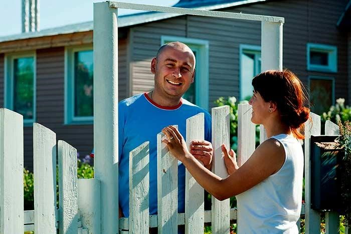 neighbors talk over fence
